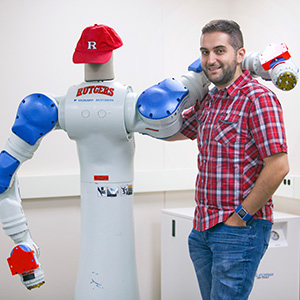 Kostas Bekris posing with a robot from the Computer Science lab